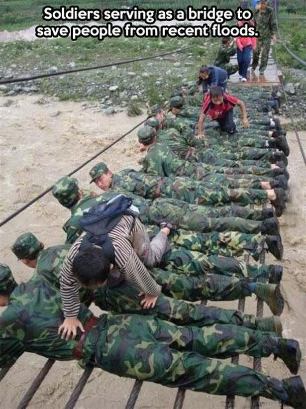 Soldiers serve as a bridge to save people from flooding.